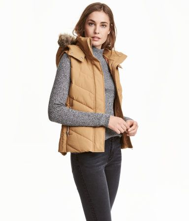 Beige. Fitted, padded vest. Detachable, lined hood with detachable faux fur trim. Stand-up collar, zip and wind flap at front with concealed snap fasteners