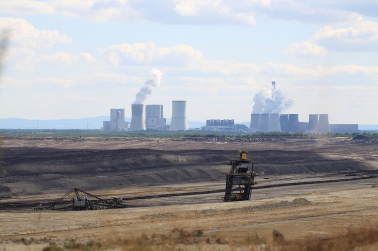 The image shows a brown coal open pit in Germany. In the background a coal plant owned by the Swedish energy giant Vattenfall.