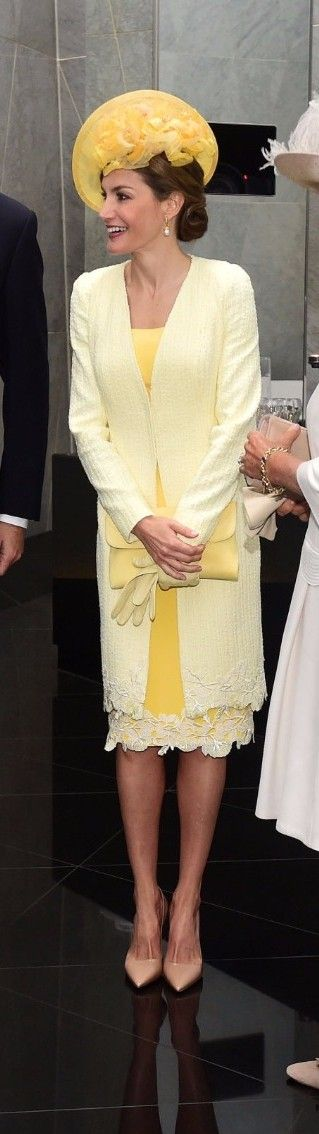 Queen Letizia wore a yellow bespoke  ensemble by Felipe Varela. The set consisted of a lemon hued dress guipure lace hem, a lighter shade summer tweed coat with the same trim, which also defined the back waist, hat, by María Nieto, and gloves in a matching tone, Prada pointy-toe pumps in nude patent leather, a new yellow leather flap clutch bag by Magrit, and pearl drop earrings  Queen Sofia. Queen Letizia of Spain at the official welcome ceremony on July 12, 2017 in London, England.