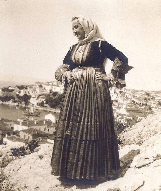 Traditional costume from Skiathos island. Greece. 1937 Φορεσιά από τη Σκοάθο Τα πολύτιμα υλικά, η εναλλαγή των χρωμάτων και η αρτιότητα της κατασκευής είναι τα κύρια χαρακτηριστικά της γιορτινής φορεσιάς της Σκιάθου. Αποτελείται από το άσπρο μεταξωτό πουκάμισο, το εξωτερικό κόκκινο μεταξωτό πουκάμισο, κεντημένο στα μανίκια, το κόκκινο, ατλαζένιο, πολύπτυχο φουστάνι στολισμένο στον ποδόγυρο με πολύχρωμο χρυσοΰφαντο ύφασμα καθώς και από το μεταξωτό μαντήλι της μέσης. Τη φορεσιά συμπληρώνει το…