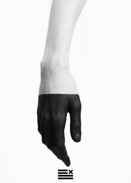 mano negra pintada en el rostro tapando la boca, y la mano real pintada de negro apuntando