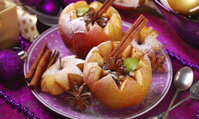 Manzanas asadas en el horno rellenas de nueces y pasas con canela, un postre muy fácil ideal para preparar en otoño o servir en Navidad.