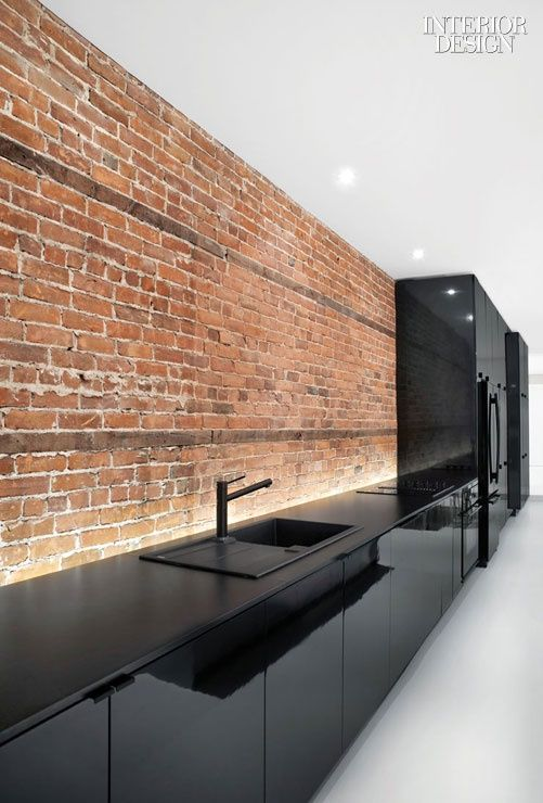 Kitchen cabinetry hugs the apartment's original brick wall.