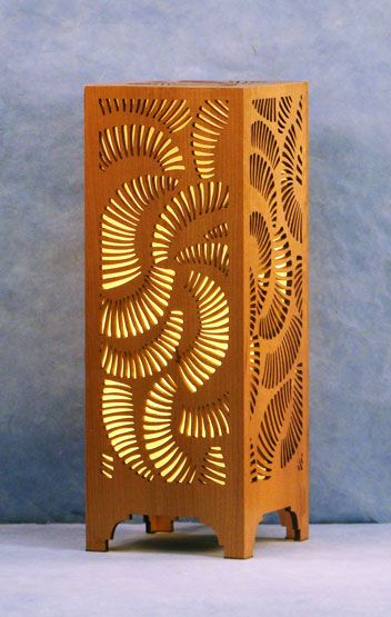 Decorative laser cut wood table lamp. Light is diffused by hand made paper and lit by a 13 watt compact fluorescent bulb.