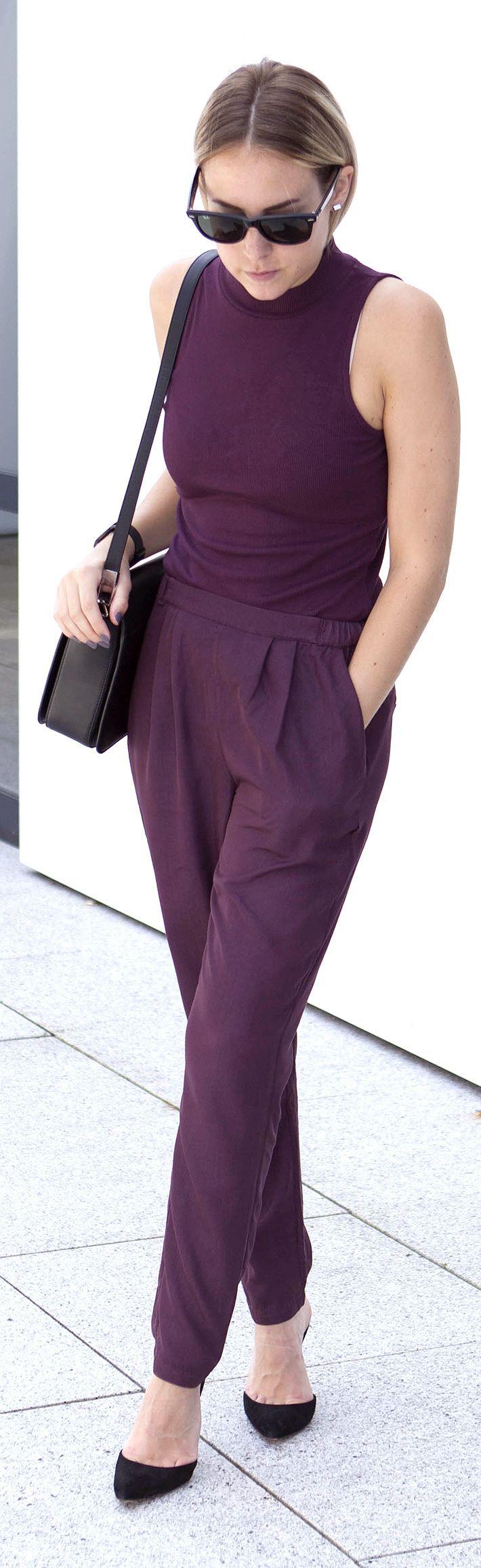 purple jumpsuit with minimal black accessories