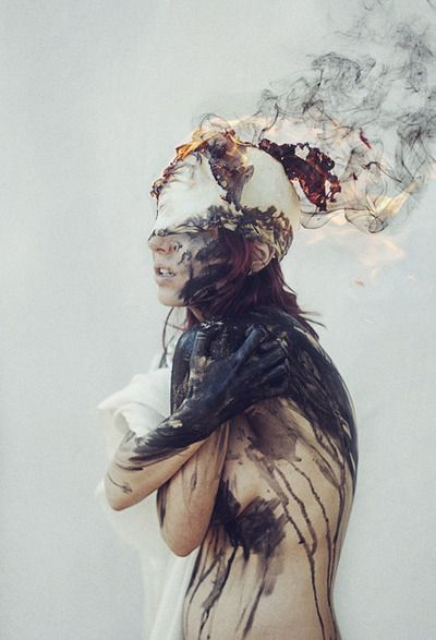 The black paint might representing where the pain created by anxiety is found. She is covering her chest to either protect herself or ease the pain.  The head, is exploding - overthinking.