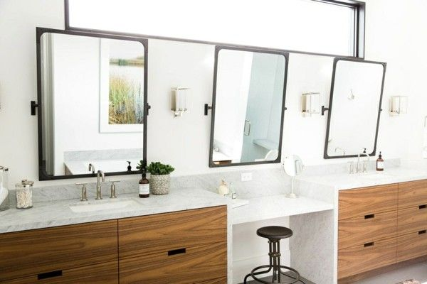 drei geometrisch geformte Spiegel großes Fenster darüber Waschbecken Waschtische Schminktisch ein edles Flair