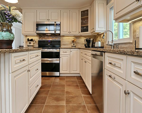 Antique White cabinets with a Walnut Glaze in Breckenridge Square style perfectly pair with the neutral variants in the Cambria Quartz countertop in Canterbury. The Corian backsplash in Sandalwood with an Offset Diamond pattern is both beautiful and durable. www.kitchenmagic.com