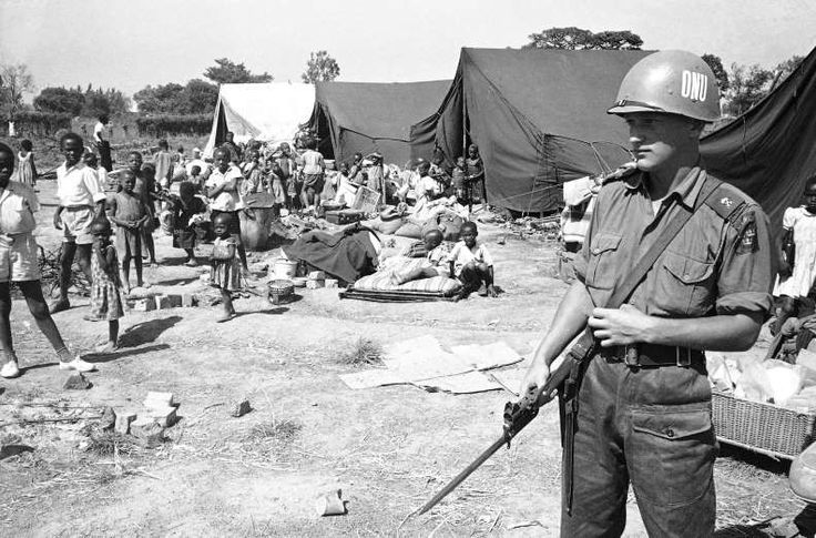 Baluba youngsters are grouped round their families' belongings while their parents register after arriving at a United Nations administered tent camp in the Elisabethville District, Katanga, Congo on Sept. 2, 1961. In foreground is a Swedish U.N. soldier
