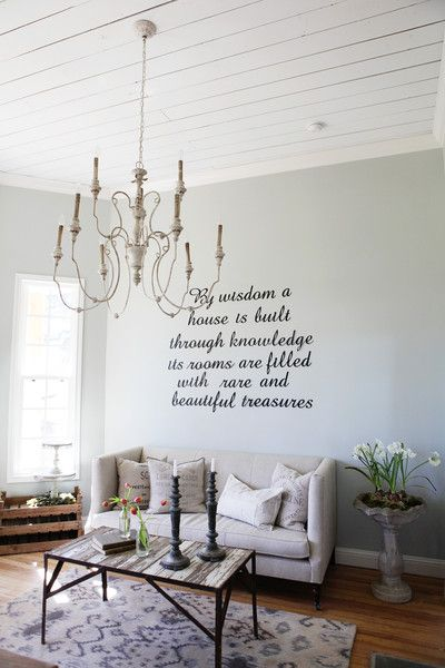 This room, which can double as an office, is mainly white but decorated with a mix of vintage finds like a delicate chandelier and interesting planters. Need proof? Just read the wall!    - CountryLiving.com