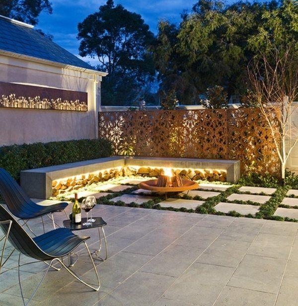 Des panneaux décoratifs métalliques et foyer central extérieur