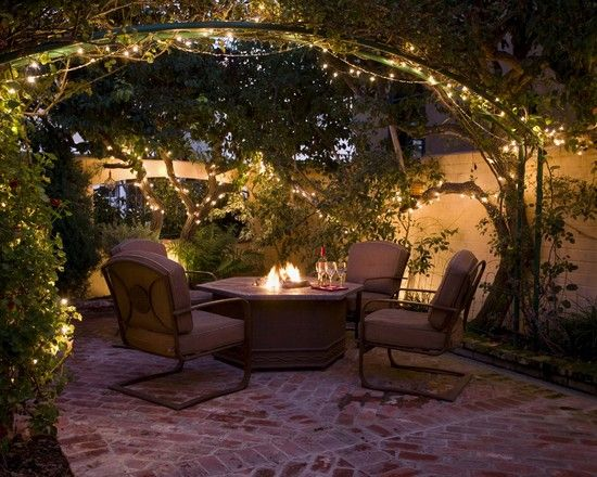 Garden. Twinkling fairy lights in an arbour set off a raised fire pit and seating area.