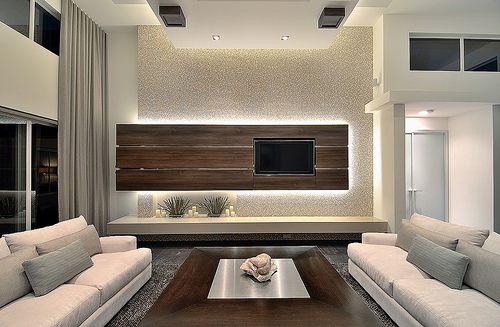 el cuarto de estar tiene muchos colores en contraste, sobre todo el marrón claro. tiene muchas ventanas y estàn dos sofás de piel clara. por encima de la península está la luz que se filtra a través de una placa de madera.