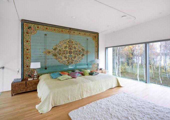 Stěnu ložnice krášlí jeden z dvanácti kusů stropních panelů ze starého rozebraného paláce indického mahárádži. Lůžko vyrobené na míru truhláři z Pentiku doplňují vyřezávané truhly, které slouží jako noční stolky. Po obou stranách přímo z postele mohou manželé pozorovat les, jezero a také polární záři