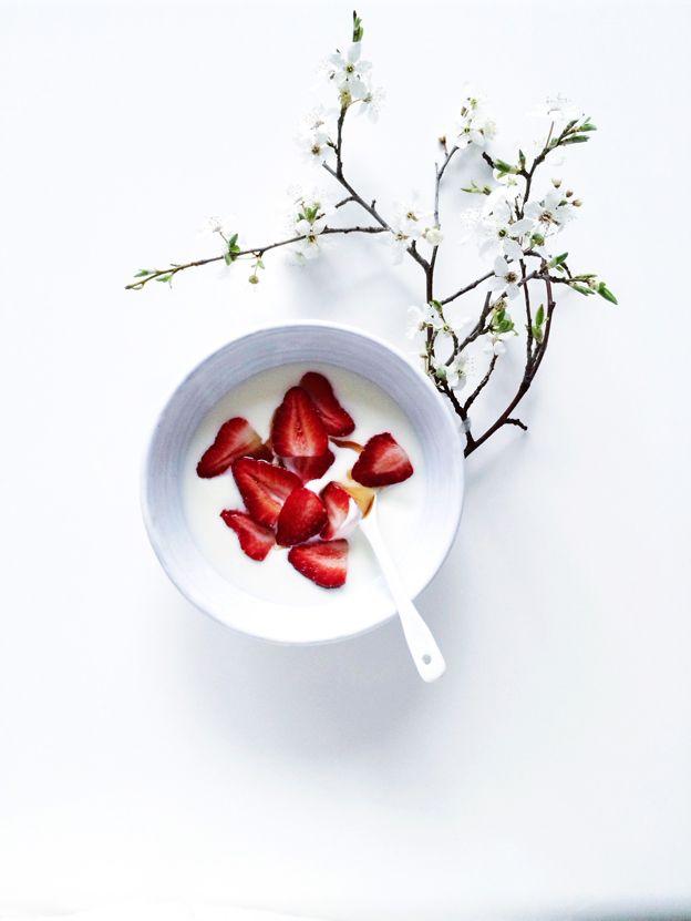 Yogurt with strawberries on white.