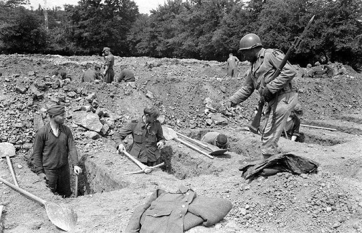 https://flic.kr/p/Pb1JNd | LC001806 | Au cimetière provisoire d'Orglandes, des prisonniers allemands creusent des tombes sous la surveillance d'une sentinelle américaine ; un « colored » armé d'un fusil Springfield 1903 avec baïonnette au canon. Le GI porte le patch First US Army. Le 18 juin 1944, le 4th Platoon, 603rd Quartermaster Graves Registration Company de la First US Army se dirige vers Orglandes pour établir un nouveau cimetière. A l'origine prévu pour les troupes américaines, il…