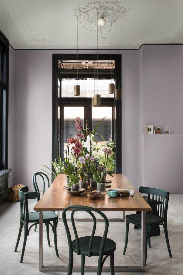 Cette salle à manger en impose par son utilisation toute en mesure de la couleur : violet poudré sur les murs, vert tropical pour les chaises et bleu gris au plafond. On adore !