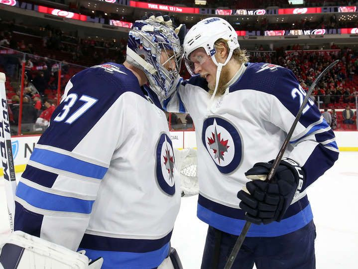 RALEIGH, NC - MARCH 4: Patrik Laine #29 and Connor Hellebuyck #37 of the Winnipeg Jets celebrate their team's victory over the Carolina Hurricanes following an NHL game on March 4, 2018 at PNC Arena in Raleigh, North Carolina. (Photo by Gregg Forwerck/NHLI via Getty Images)