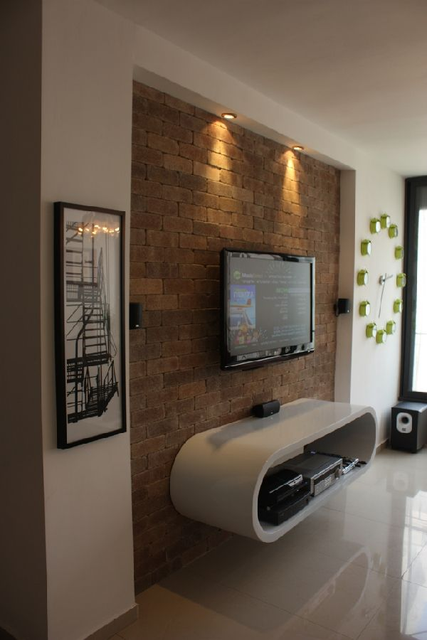 Love the texture of the wall with the modern floating cabinet and mounted TV. Simple and clean and contemporary.