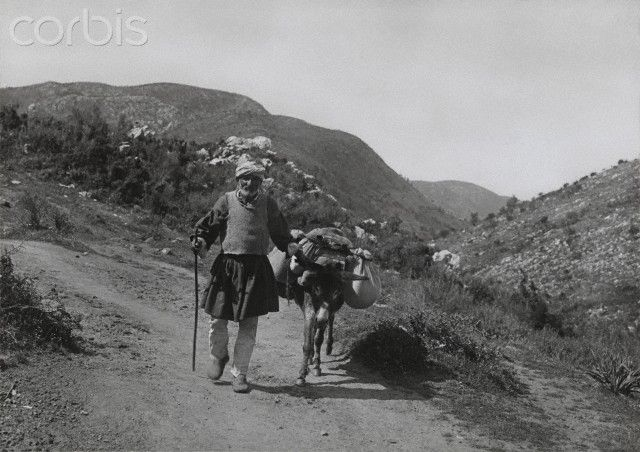 An elderly man and his donkey travel along a Greek mountain road-Fred Boissonnas