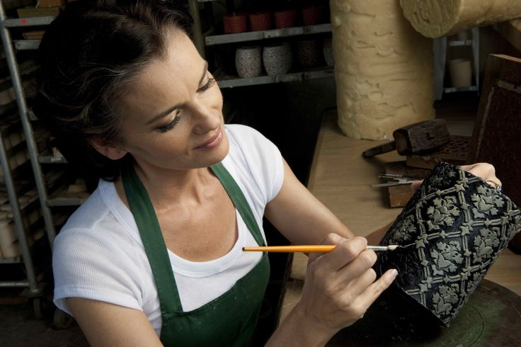Creative Director, Kelly Marciano, painting a black Damask pillar.
