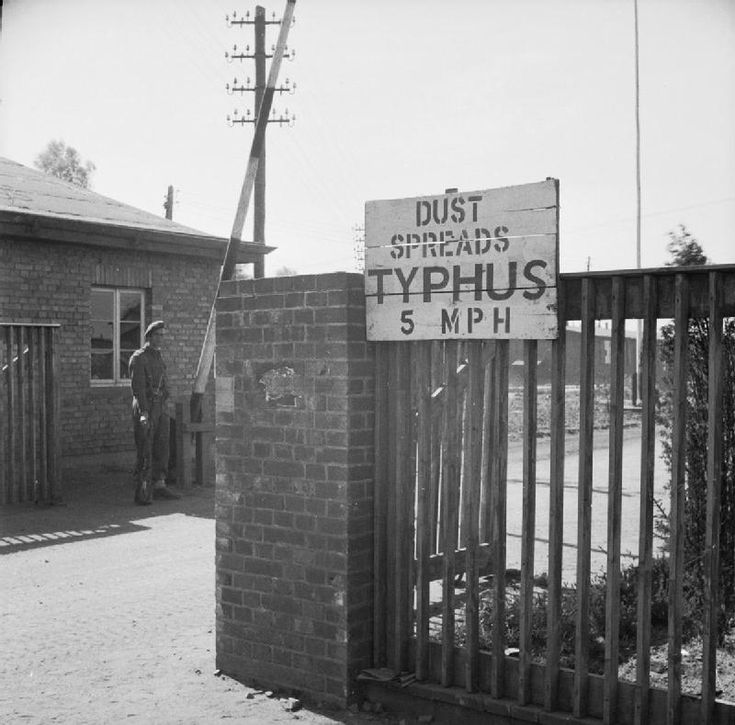 "THE LIBERATION OF BERGEN-BELSEN CONCENTRATION CAMP, APRIL 1945. A sign at the entrance to Belsen reading ""Dust spreads typhus - 5 mph"". This speed restriction was imposed to prevent the spread of dust carrying the lice which were infested with typhus."