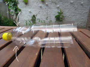 De drainagegaatjes komen vlakbij de dop van de fles, in het aflopende gedeelte.