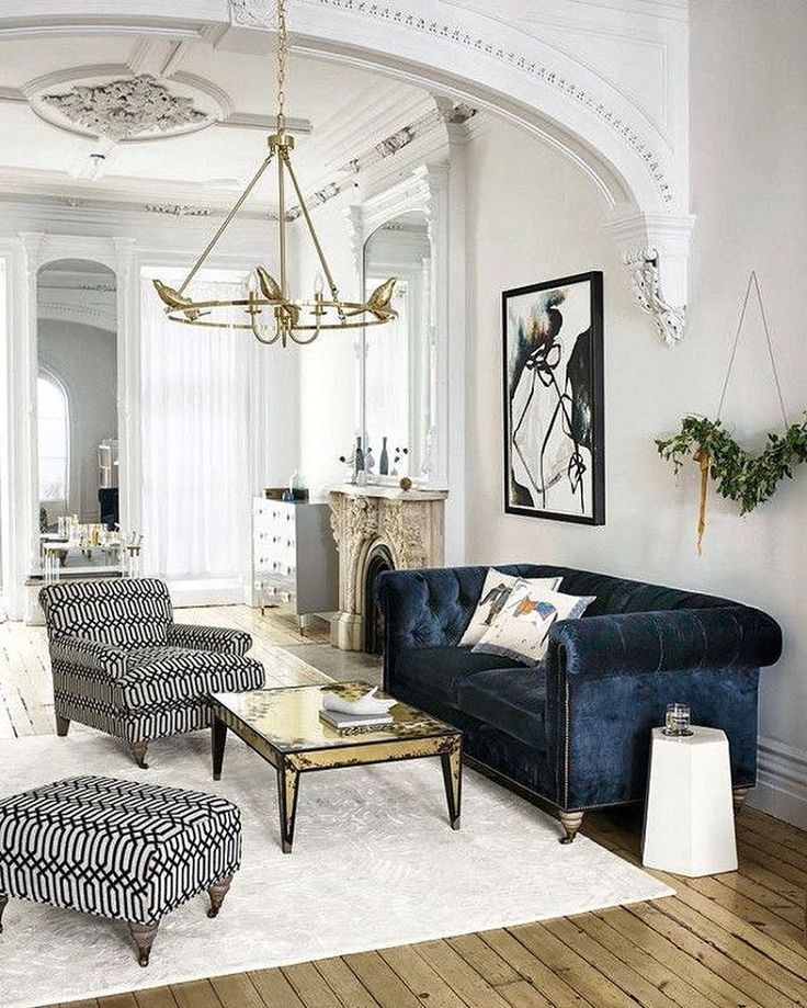 10 insider tips from an anthropologie stylist living room with classic architectural details a blue velvet upholstered couch and a low hanging gold