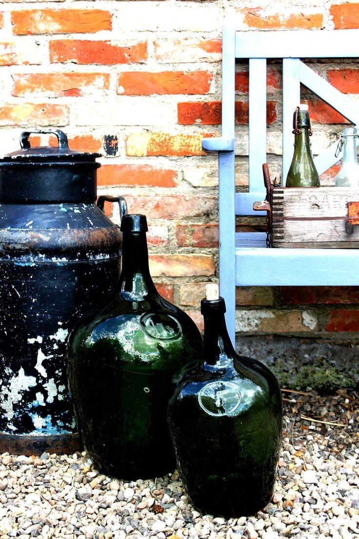 Gammel mælkejunge, mundblæste glasflasker til 5 og 10 liter, en gammel flaskekasse og en slidt bænk.