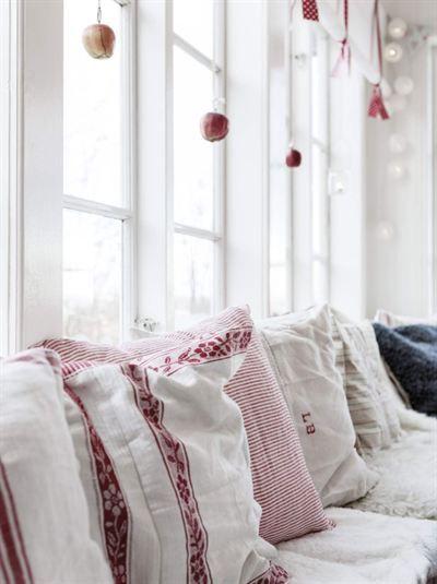 1800-TALSHUSET DÄR DET PYNTAS SOM FÖRR I TIDEN: Vid fönstren står en platsbyggd soffa som sträcker sig i vinkel runt bordet och är omsorgsfullt pyntad med mjuka fårskinn, och vackra kuddar sydda av gamla kökshanddukar | Leva & Bo