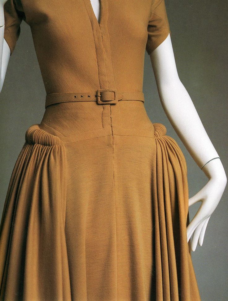 A closeup shot of a 1950 afternoon dress by Madame Grés shows painstaking gathers at the hip that flare into perfect, flattering pleats. The...