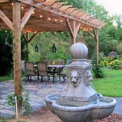 A pergola, Italian String lights, pea gravel, kitchen garden, flag stone, lanterns and fountain all come together.