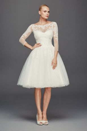 Inspired by 1950s couture, this short tulle wedding dress is classic with a vintage appeal. Shimmering lace appliques adorn the illusion 3/4 sleeves and neckline, and the full skirt was designed for dancing.  Truly Zac Posen, exclusively at David's Bridal  Also available in Plus Size, Extra Length and Plus Size Extra Length. Check your local stores for availability.  Fully lined.