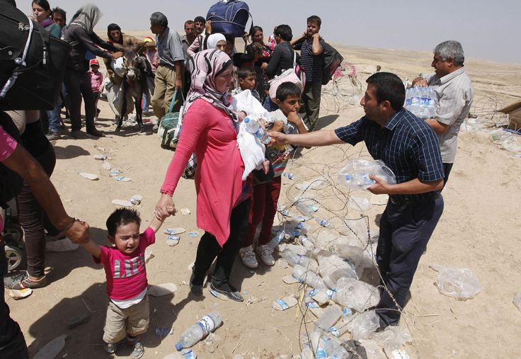 Iraqi officials distribute water to Syrian refugees as they cross into Iraq at the Peshkhabour border point in Dahuk, on August 20, 2013. Around 30,000 Syrians, the vast majority of them Kurds, fled the region over a five-day stretch and crossed the border to the self-ruled Kurdish region of northern Iraq.