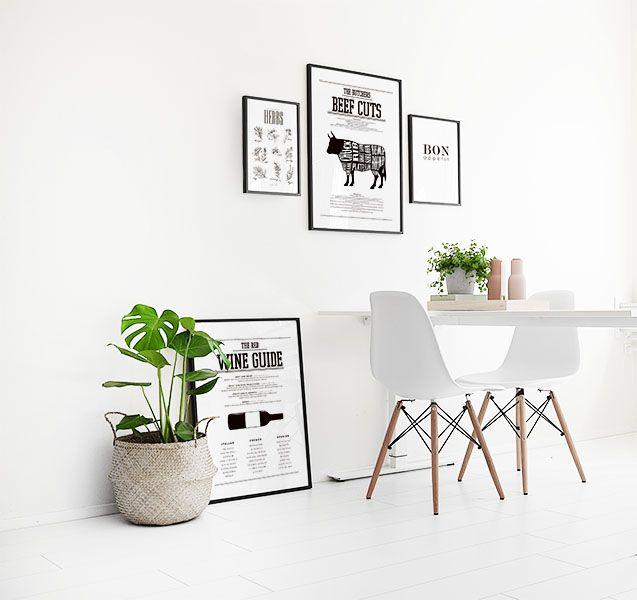 Snygg inredning med tavlor och gröna växter i köket. Inredningsdetaljer i svartvitt till kök. Stilren och sober inredning i vitt.