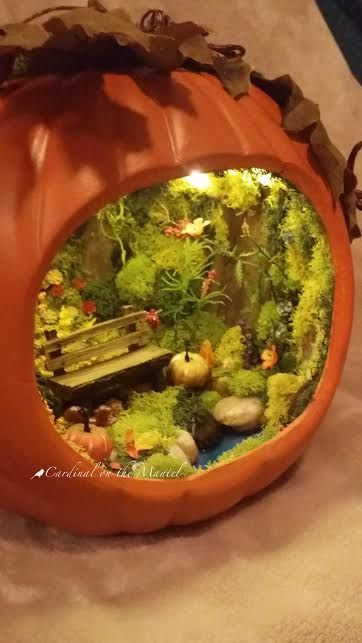 Fairy Garden in Pumpkin by Cardinal on the Mantel.  Note lights and pond!