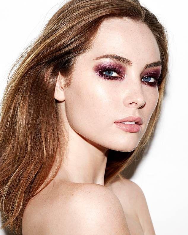 Inspiração de make de olho incrível em tons de vinho com muito brilho. No rosto, pele iluminada com maquiagem leve.