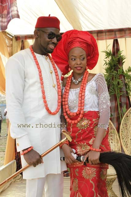 Igba Nkwu Nwanyi igbo wedding couple. Chief red hat. And Lolo. Nigerian traditional wedding. Red and white African fabric. coral beads