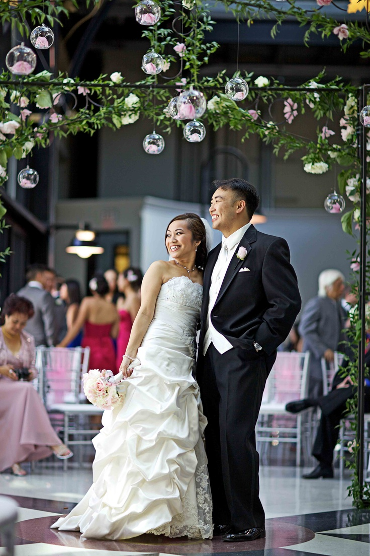 The newlyweds under the ivy and flower covered ceremony gazebo; Hanging glass orbs filled with pink roses, orchids, and LED lights; Fairmont Palliser Wedding; Calgary wedding planner and decorator (Photo by Andras Schram Photography)