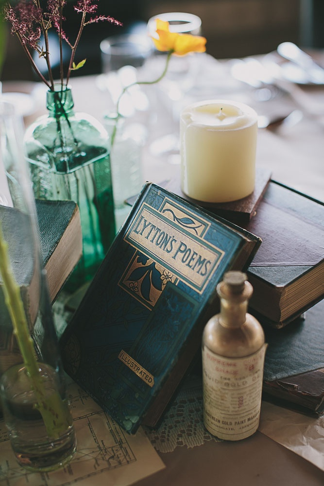 Antique books, coloured glasswear and candles
