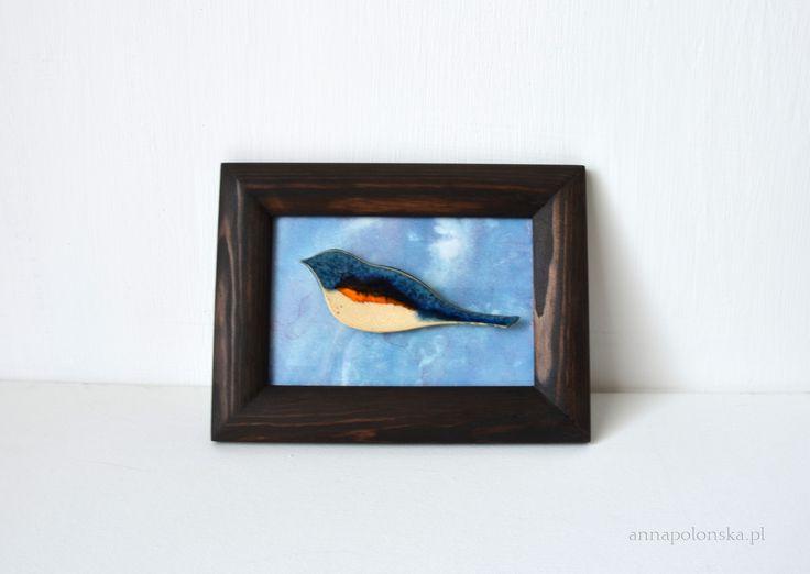 """""""Obraz z ceramicznym ptakiem IV"""", 15x20 cm; Ceramiczny obraz jest unikalną dekoracją wnętrza.  Obraz łączy w sobie różne techniki.  Element obrazu – biała glina ceramiczna;  Tło – tusz/akryl na papierze; zabezpieczone szklaną szybką.  Obraz sprzedawany jest w drewnianej ramie."""