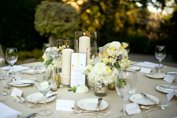 Pillar candles and several smaller flower arrangements are