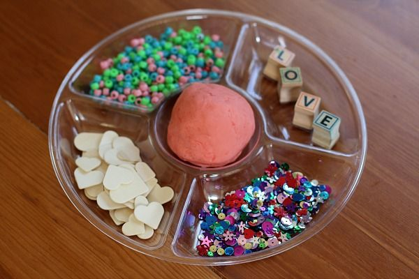 This invitation to create with cherry play clay was an absolute hit with my toddler! Make some cherry play clay, grab a few simple materials, and you're ready to set up this fun sensory play activity perfect for Valentine's Day!