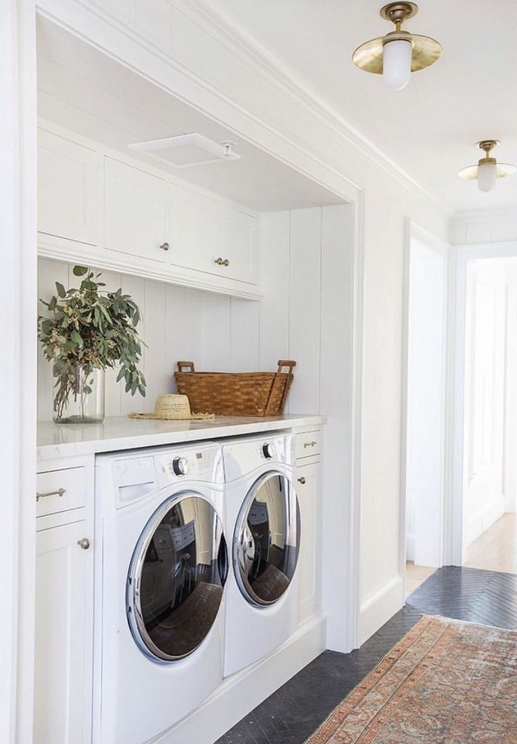 Laundry Room white cabinets planked walls brass