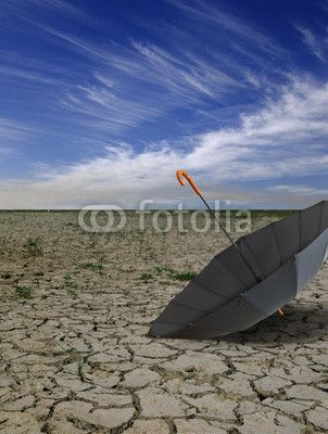 Dry deserted landscape with open black umbrella.