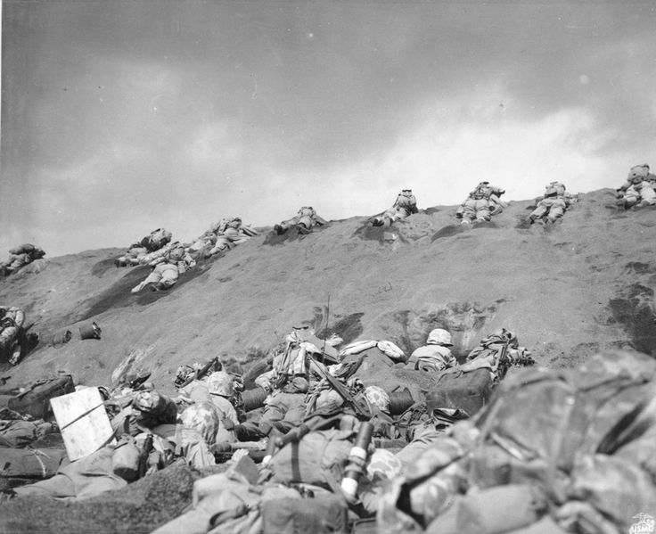 Red Beach One, Iwo Jima, 1945. Photo caption: Iwo Jima February 19, 1945. In the face of withering enemy fire, Fifth Division Marines work their way up the slope from Red Beach One toward Suribachi Yama, hidden in the pal of smoke. From the Photograph Collection at the Marine Corps Archives and Special Collections OFFICIAL USMC PHOTOGRAPH