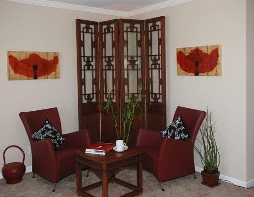 Chinese antique screen and table side-by-side with contemporary Italian leather chairs