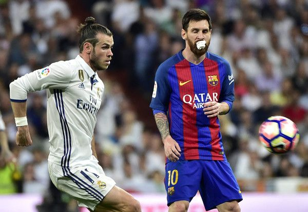 Real Madrid's Welsh forward Gareth Bale (L) vies wit Barcelona's Argentinian forward Lionel Messi during the Spanish league football match Real Madrid CF vs FC Barcelona at the Santiago Bernabeu stadium in Madrid on April 23, 2017. / AFP PHOTO / GERARD JULIEN