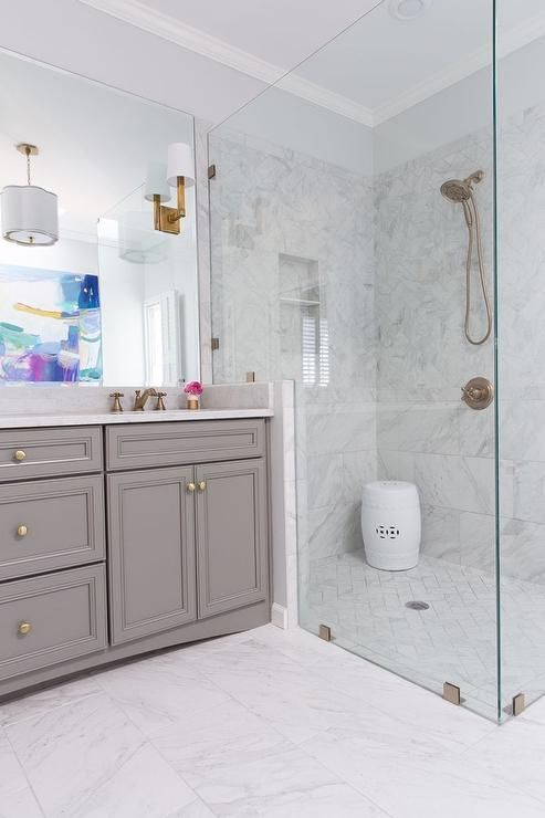 Stunning bathroom features a gray vanity painted Benjamin Moore Chelsea Gray adorned with gold hardware paired with a porcelain marble look countertop under a frameless mirror illuminated by E.