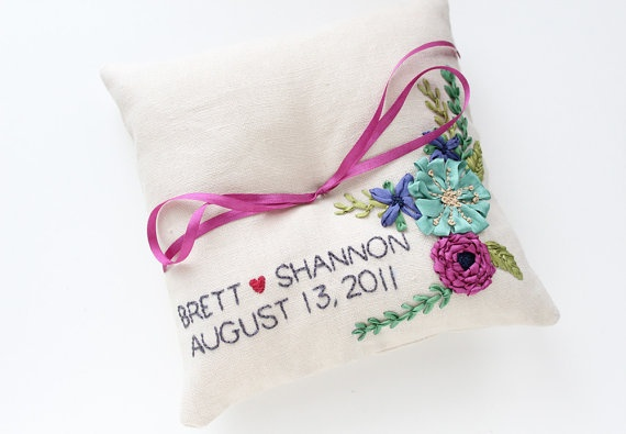 bright flowers with the couple's names on a beautiful ring pillow
